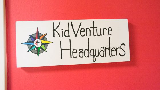 A photograph of the KidVenture logo posted outside the main headquarters office inside Trinity church.